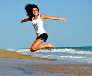 confident woman smiling and jumping on beach