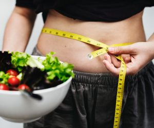 woman's stomach losing weight and eating healthy food