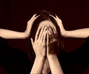 woman experiencing panic attack with hands covering face